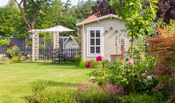 English garden in summer with summerhouse with trees, plants and flowers.