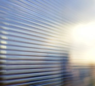 Blue surface of striped polycarbonate with a reflection of the blue distance of the city